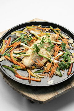 chinese style steamed fish fillet with vegetables on hot plate