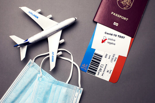 Traveling during COVID-19 virus, passport with airline ticket, covid-19 negative test, medical masks and plane on grey background, airport security health and safety check concept
