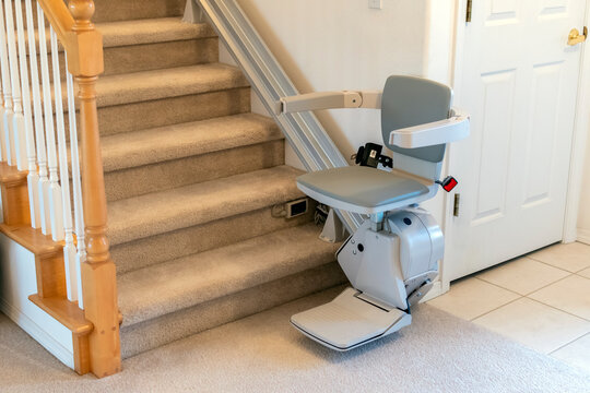 An electric, motorized chair life for persons with disabilities on a carpeted staircase in a residential home.
