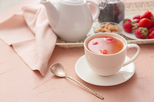 Cup of hot strawberry tea on color background