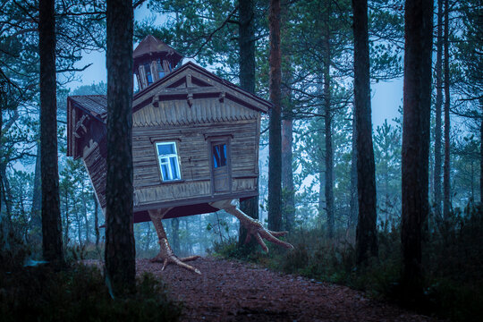 Baba Yaga witch house standing on chicken legs and walking in a night forest between trees