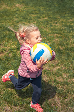 Happy running beautiful child girl with ball having fun outdoors symbolizing happy carefree childhood lifestyle