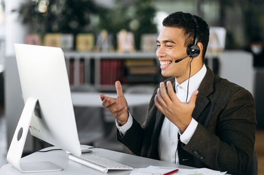 Satisfied successful hispanic business leader, manager or tutor sitting at work desk wearing headphones communicate and smiling while video conference with colleagues or students