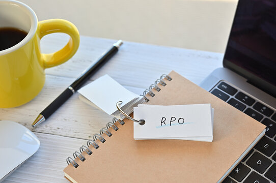 There's a word book on a desk with a cup of coffee and laptop pc. The word RPO is written in it. It's an abbreviation for Recruitment Process Outsourcing.