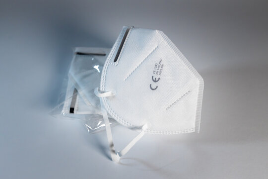 FFP2 face mask in white in front of a clean neutral background. Certified disposable protection to reduce aerosol emission during Covid-19 pandemic.