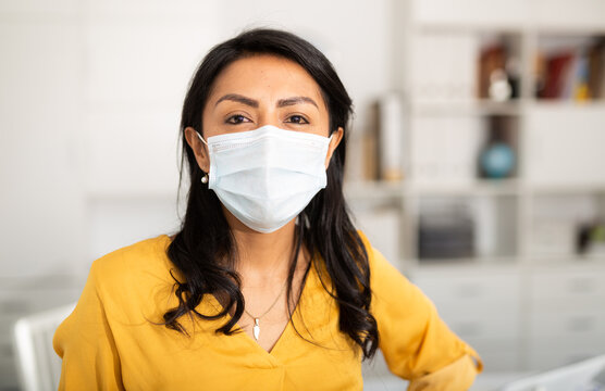 Portrait of handsome young businesswoman with surgical medical mask looking at camera. Business people medicine and health care concept. Indoor, light office room