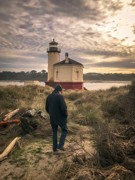 Male tourist walking towards Bandon Lighthouse in Oregon