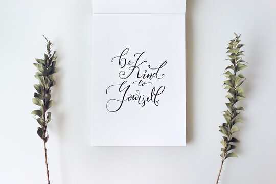 """""""Be kind to yourself"""", motivational and inspirational quote on notebook. Minimal creative flat lay with plant."""