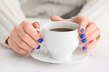 Woman with beautiful manicure and cup of coffee on table, closeup