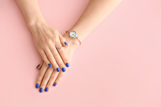 Hands with beautiful manicure on color background