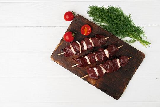 Raw beef liver kebab on skewers on wooden board