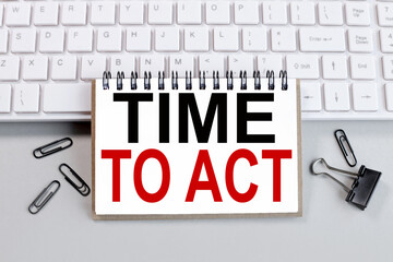 time to act, text on white paper on white keyboard
