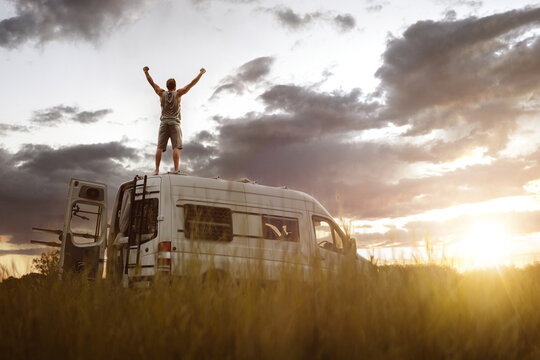 Man with raised arms on the roof of his camper van