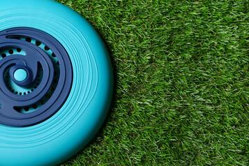 Fototapeta Light blue plastic frisbee disk on green grass, top view. Space for text obraz
