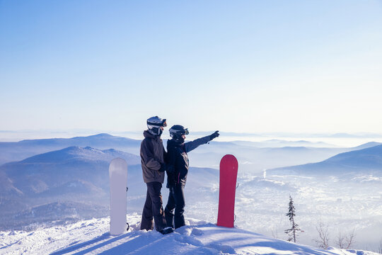 Loving couple of snowboarders hold hands and look forward, man indicates direction to woman with snowboard route with hand