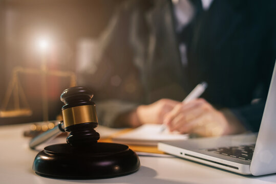 Justice and law concept.Male judge in a courtroom the gavel, working with digital tablet computer on wood table.