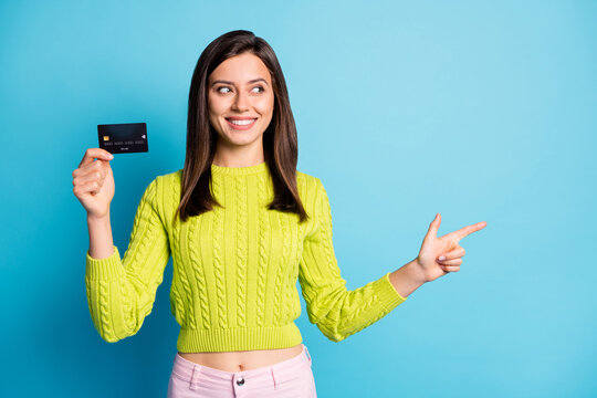 Photo portrait of woman pointing finger looking at blank space holding debit card in one hand isolated on pastel blue colored background