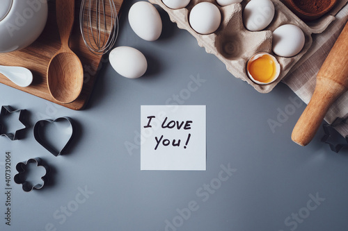 Note I love you. Ingredients for making homemade cookies on a gray background. The concept of cooking sweets for Valentine's day, Father's Day or Mother's Day. Flat lay, top view