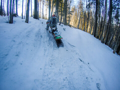 A man rides a snowbike in the mountains. View from the camera on the helmet. Motorcycle clips. Forest in winter