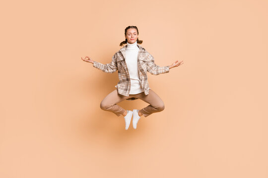 Full size photo of young beautiful attractive pretty calm peaceful girl meditating in air isolated on beige color background