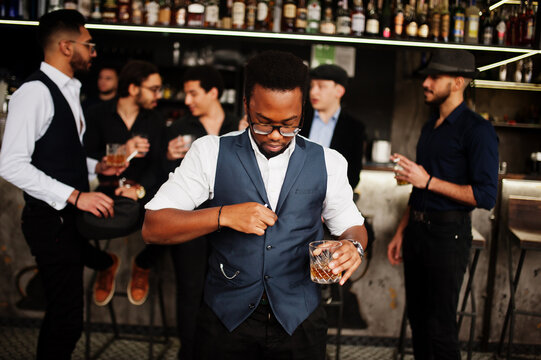Stylish african american man against group of handsome retro well-dressed guys gangsters spend time at club, drinking on bar counter. Multiethnic male bachelor mafia party in restaurant.