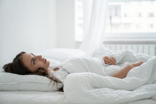 Angry woman annoyed by loud neighbors, looking up, suffering from insomnia or stress. Tired woman trying to falling asleep in bed at home in early morning. Sleep disturbance concept.