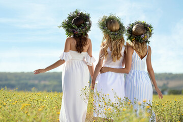 Young women wearing wreaths made of flowers in field on sunny day, back view