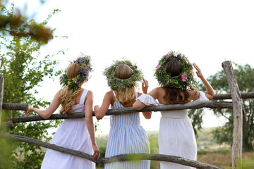 Young women wearing wreaths made of beautiful flowers near wooden fence, back view