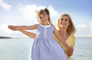 Happy mother and her child on beach. Spending time in nature