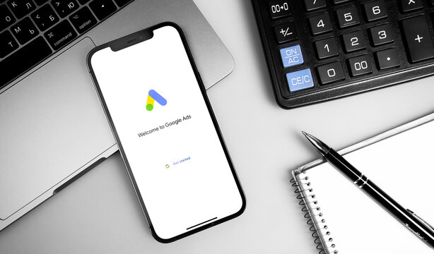 Google Ads (AdWords) logo on the screen iPhone, notebook, calculator and notepad closeup. Google is the biggest Internet search engine in the world. Moscow, Russia - December 5, 2020