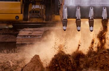Fototapeta Selective focus on metal bucket teeth of backhoe digging soil. Backhoe working by digging soil at construction site. Crawler excavator digging on soil. Earth moving machine. Excavation vehicle.