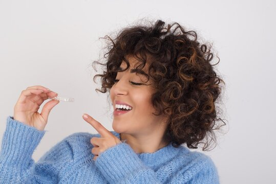 young beautiful caucasian woman wearing blue knitted sweater standing against white studio background holding an invisible aligner braces and smiling. Dental healthcare concept.