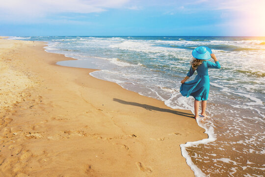 Seascape on a sunny summer day. The girl on the beach looks at the sea. Young happy girl carefree walk along the sea in blue fluttering dress and sun hat