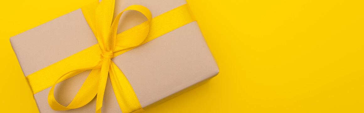 too view of wrapped present with ribbon on bow isolated on yellow, banner