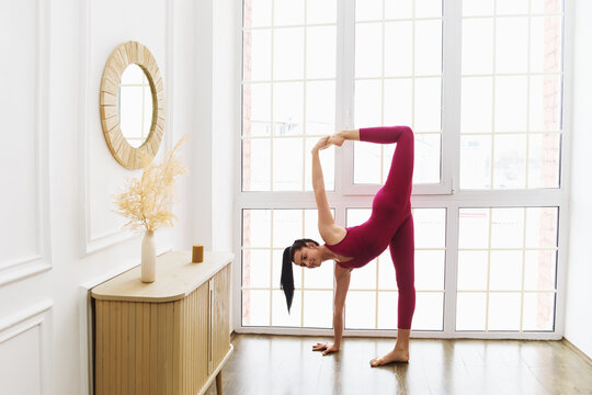 Portrait of a beautiful young woman in pink sportswear practicing yoga at home near the window performing a variation of the crescent moon pose, Ardha Chandrasana