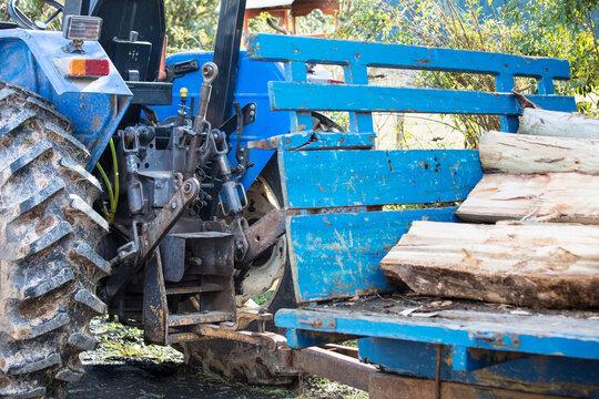 Close up de reboque com madeira atrelado ao trator agrícola