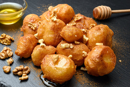 Homemade lokma served with honey, nuts and cinnamon on black dish