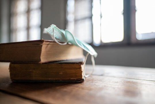 Books and hygiene masks are placed on the wooden table.