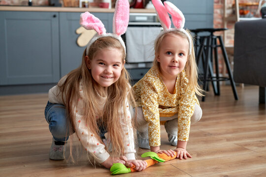 Two happy girls playing handmade carrots on the floor