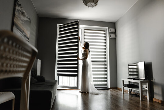 the bride is waiting for the groom in a room with blinds hanging on the window. girl at the window. silhouette of the bride. shutters on the windows. wedding day fees