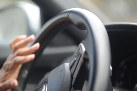Someone driving , close up hands on steering wheel