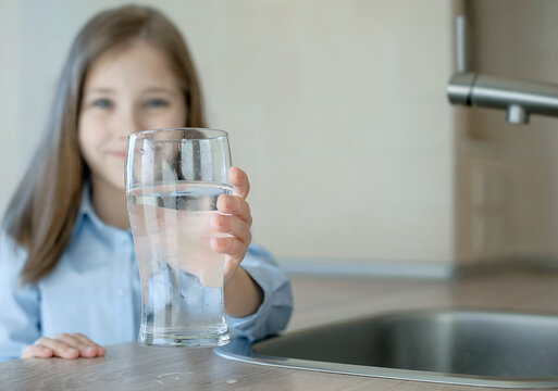 Happy little girl holding a glass of water. Selective focus on child hand with glass of water in foreground. Hydration. Water quality check. World water monitoring day. Environmental pollution problem