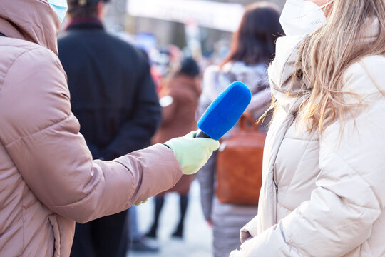 Journalist wearing protective face mask against coronavirus COVID-19 disease holding microphone making media interview during anti-vaccination protest