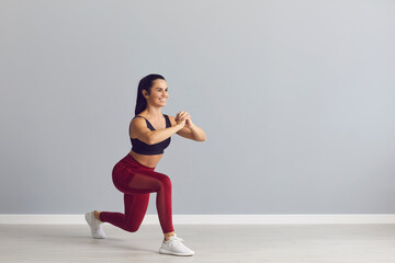 Smiling fitness trainer showing how to do fitness exercise. Happy fit young woman in sports bra and leggings doing forward lunges holding hands together in front of chest during workout at the gym