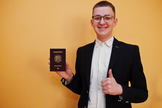 Young handsome man holding Principality of Andorra passport id over yellow background, happy and show thumb up. Travel to Europe country concept.