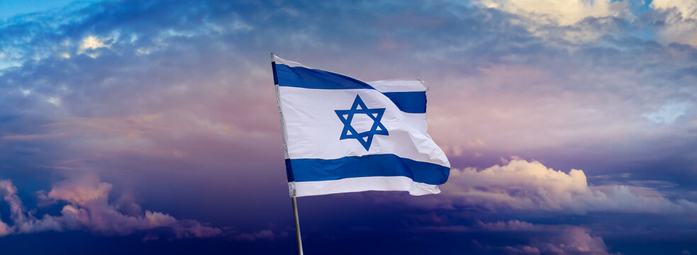 Patriotic concept about Israel with national state symbols - Israeli flag with a star of David over Jerusalem at cloudy sky background on sunset, panoramic view.