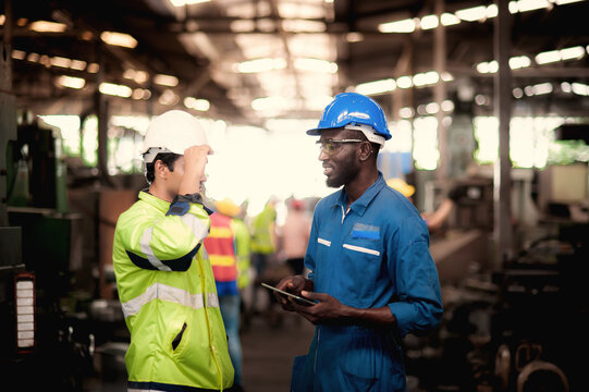 Group of industrial worker team and foreman  consist of Technicians, Engineers is discussing and working with many equipment and machine in Industry plant.
