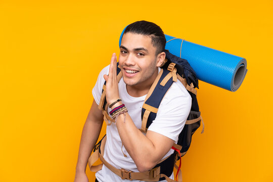 Young mountaineer asian man with a big backpack isolated on yellow background whispering something