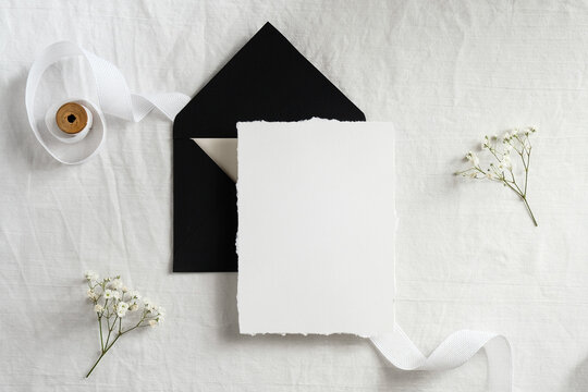 Wedding invitation template. Black envelope and blank card on textile background with ribbon and flowers. Elegant wedding flat lay composition.