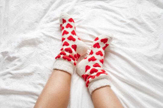 women's feet in warm socks with red hearts on a white bed